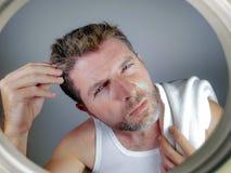 Портрет образа жизни привлекательного потревоженного и, который отнесенного кавказского человека смотря зеркало ванной комнаты на Стоковые Изображения