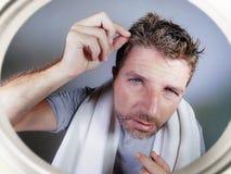 Портрет образа жизни привлекательного потревоженного и, который отнесенного кавказского человека смотря зеркало ванной комнаты на Стоковое Фото