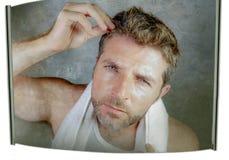 Портрет образа жизни привлекательного потревоженного и, который отнесенного кавказского человека смотря зеркало ванной комнаты на Стоковые Фото