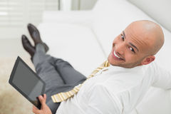 Портрет облыселого бизнесмена с цифровой таблеткой на софе Стоковое Изображение