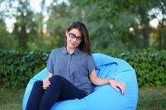 Портрет довольно женского кто сидело в стуле и представлять для photog Стоковое Изображение