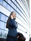 Портрет довольно молодой бизнес-леди говоря на телефоне около здания Стоковая Фотография