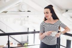 Портрет довольно молодой женщины брюнет имея чашку кофе в кафе смотря прочь Стоковая Фотография
