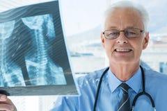 Портрет доктора анализируя отчет о рентгеновского снимка Стоковые Изображения