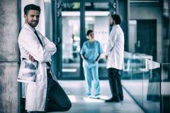 Портрет доктора держа рентгеновский снимок пока стоящ против стены Стоковая Фотография