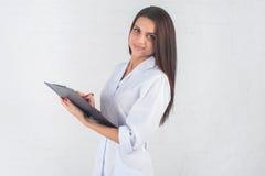Портрет доктора женщины на коридоре больницы, держащ планшет, смотрящ камеру, усмехаясь Стоковые Изображения RF