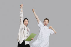 Портрет доктора и пациента веселя вверх с поднятыми оружиями Стоковые Изображения