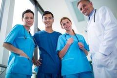 Портрет доктора и хирургов стоя совместно в коридоре Стоковое Изображение RF