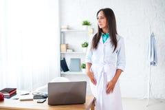 Портрет доктора молодой женщины при белое пальто стоя в медицинском офисе Стоковое Фото