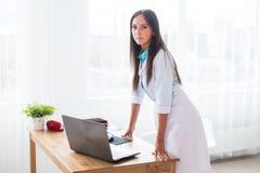 Портрет доктора молодой женщины при белое пальто стоя в медицинском офисе смотря камеру Стоковые Фото