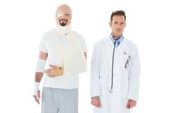 Портрет доктора при пациент связанный вверх в повязке Стоковые Изображения