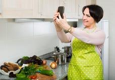 Портрет домохозяйки в рисберме делая selfie в отечественной кухне Стоковое Изображение