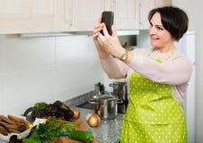 Портрет домохозяйки в рисберме делая selfie в отечественной кухне Стоковые Изображения