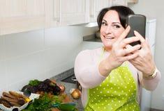 Портрет домохозяйки в рисберме делая selfie в отечественной кухне Стоковое Фото
