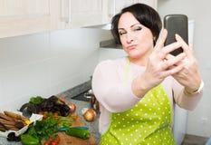 Портрет домохозяйки в рисберме делая selfie в отечественной кухне Стоковое фото RF