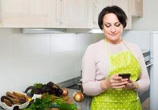 Портрет домохозяйки в рисберме получая sms с рецептом Стоковые Изображения