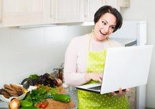 Портрет домохозяйки в рисберме с компьтер-книжкой на кухне Стоковое Фото