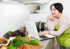 Портрет домохозяйки в рисберме с компьтер-книжкой на кухне Стоковые Изображения