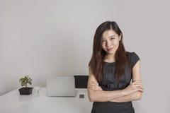 Портрет оружий уверенно молодой коммерсантки стоящих пересек в офис Стоковое Фото