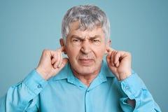 Портрет осадки надоел зрелые уши штепсельных вилок человека при пальцы, одетые в официально рубашке, представления против голубой стоковые фото