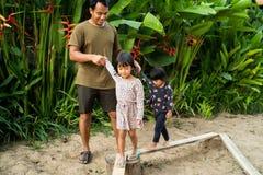 Портрет отец помогая дочери 2 с удерживанием его руки при игре коромысла стоковое фото