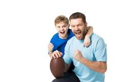 Портрет отца и сына держа шарик рэгби и смотря камеру Стоковые Фотографии RF