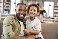 Портрет отца и сына сидя на софе в салоне совместно стоковые фотографии rf