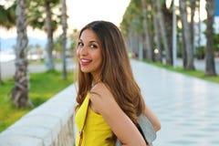Портрет от задней части привлекательной девушки усмехаясь на камере и идя в улицу Стоковые Изображения RF