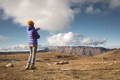 Портрет от задней части путешественника девушки в куртке с крышкой и рюкзаком стоит на предпосылке эпопеи стоковая фотография rf