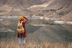 Портрет от задней части путешественника девушки сфотографировать на предпосылке озера в горах в осени или стоковое изображение
