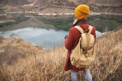 Портрет от задней части путешественника фотографа девушки на предпосылке озера в горах в осени или предыдущий стоковые фото