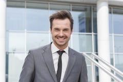 Портрет офисного здания счастливого молодого бизнесмена стоящего внешнего Стоковые Фотографии RF