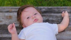 Портрет очаровательной маленькой девочки в белом bodysuit лежа на деревянной поверхности сток-видео