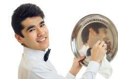Портрет очаровательного молодого кельнера с черными волосами которые бортовой поднос и усмехаться Стоковая Фотография