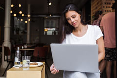 Портрет очаровательной латинской женщины имея видеоконференцию на ее сет-книге во время перерыв на ланч в современной кофейне Стоковые Изображения RF