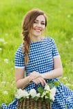 Портрет очаровательной девушки с корзиной цветка на лужайке Стоковое фото RF