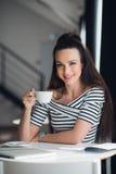 Портрет очаровательной женщины сидя на таблице и держа чашку чаю смотря камеру Стоковое фото RF