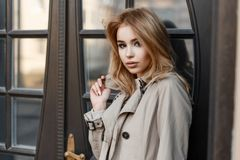 Портрет очаровывать милую молодую женщину в стильном пальто весны на предпосылке деревянной винтажной двери ресторана стоковое изображение