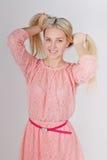 Портрет очень привлекательной усмехаясь блондинкы, заплетая отрезки провода Стоковая Фотография
