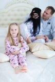 Портрет дочери обнимая и усмехаясь, hoiling подушка сердца влюбленности Стоковые Изображения RF