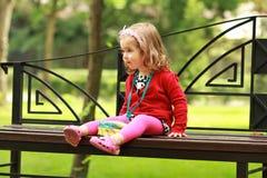 Портрет один годовалый милой маленькой курчавой девушки нося красный кардиган и держатель при шар сидя на стенде в парке Стоковые Фото
