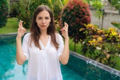 Портрет пальцев крестов молодой женщины с надеждой что-то приходит истинный, бассейн на предпосылке стоковая фотография rf