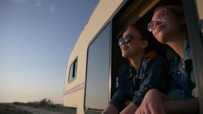 Портрет пары молодых женщин одетых в джинсах в окне autotrailer сток-видео