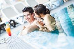 Портрет пары усмехаясь и выпивая коктеиль в бассейне Стоковая Фотография RF