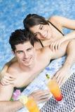 Портрет пары усмехаясь и выпивая коктеиль в бассейне Стоковая Фотография