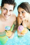 Портрет пары усмехаясь и выпивая коктеиль в бассейне Стоковые Изображения