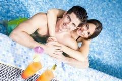 Портрет пары усмехаясь и выпивая коктеиль в бассейне Стоковое фото RF