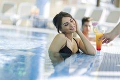 Портрет пары усмехаясь и выпивая коктеиль в бассейне Стоковые Фото