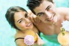 Портрет пары усмехаясь и выпивая коктеиль в бассейне Стоковые Изображения RF