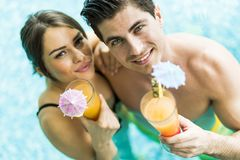 Портрет пары усмехаясь и выпивая коктеиль в бассейне Стоковое Фото